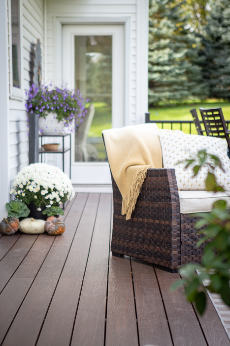 deck with chair and blanket surrounded by mums